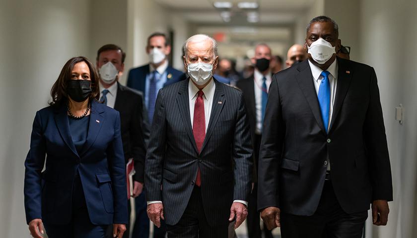 Joe Biden walking with his administration, wearing masks