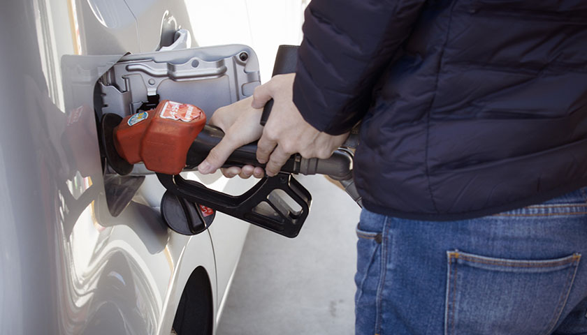 Person pumping gas into vehicle