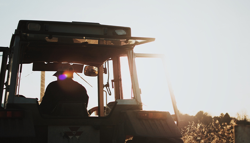 Silhouette of man on a tractor during golden hour