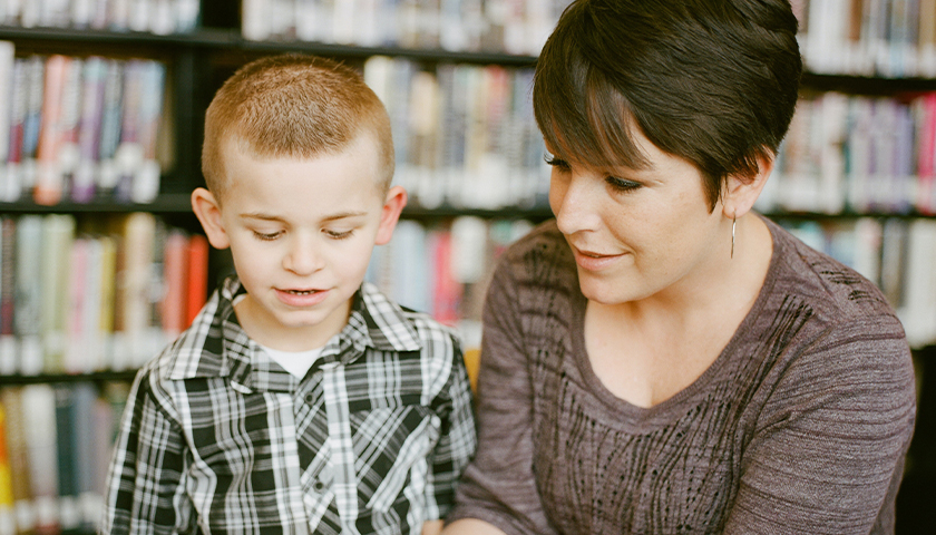 Teacher holding book, reading to boy student