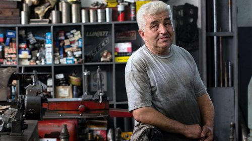 Man in gray shirt, standing in a shop