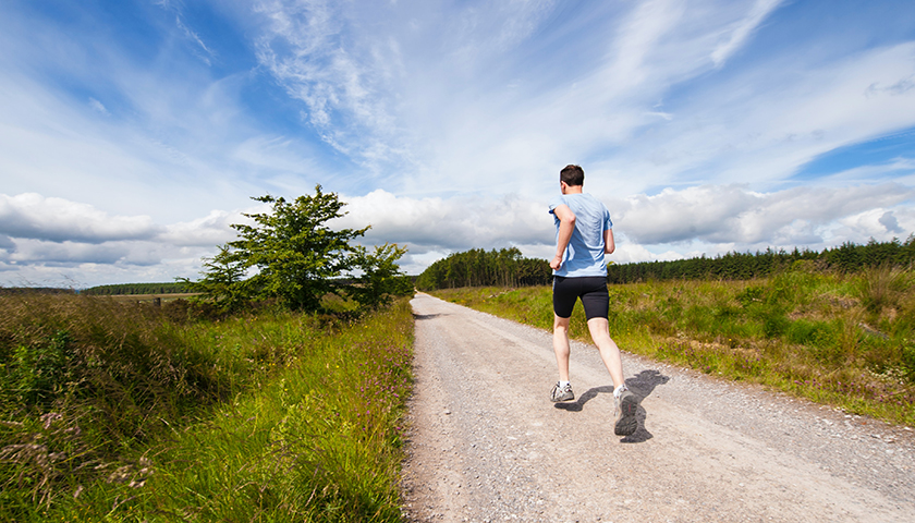 Man running on a gravel road during the day with a blue shirt on