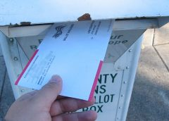 Person putting mail-in ballot in ballot return box