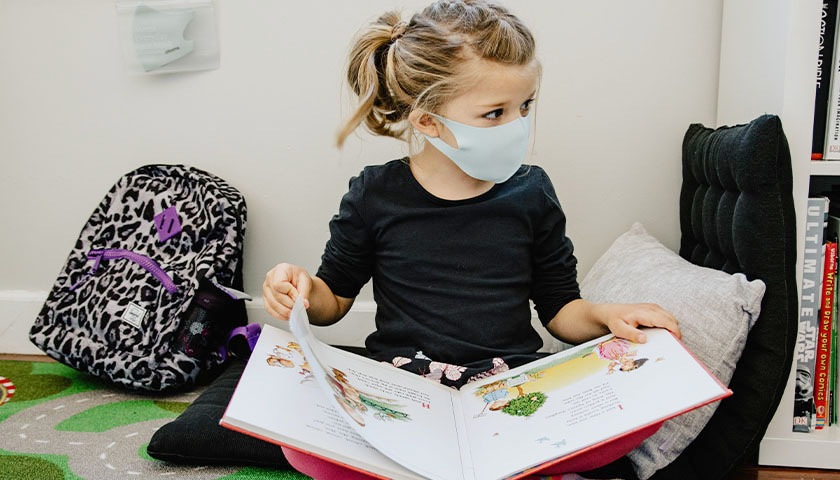 Young girl wearing a mask and reading a book in school