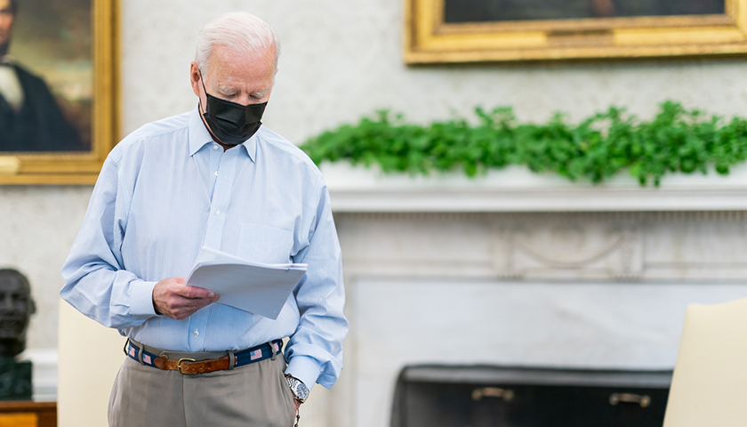 Joe Biden with black mask on, looking at papers in hand