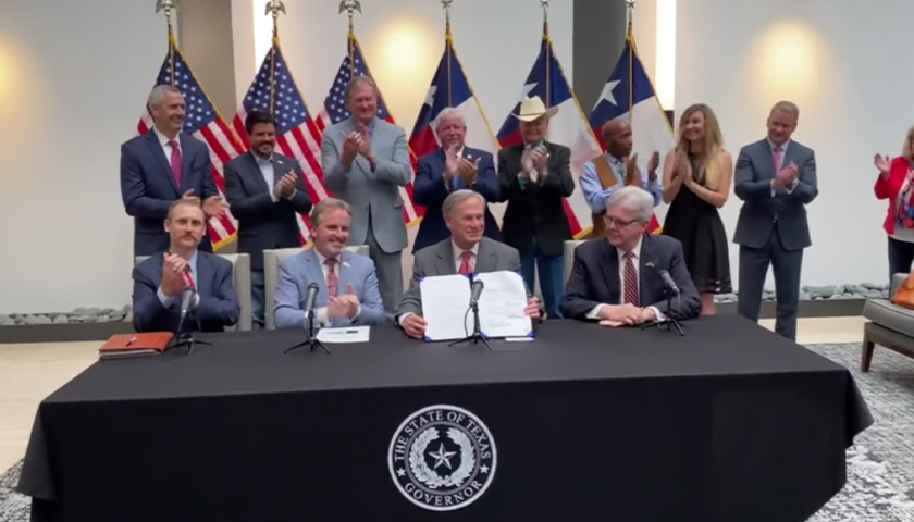 Greg Abbott holding recently signed Texas voting reform bill